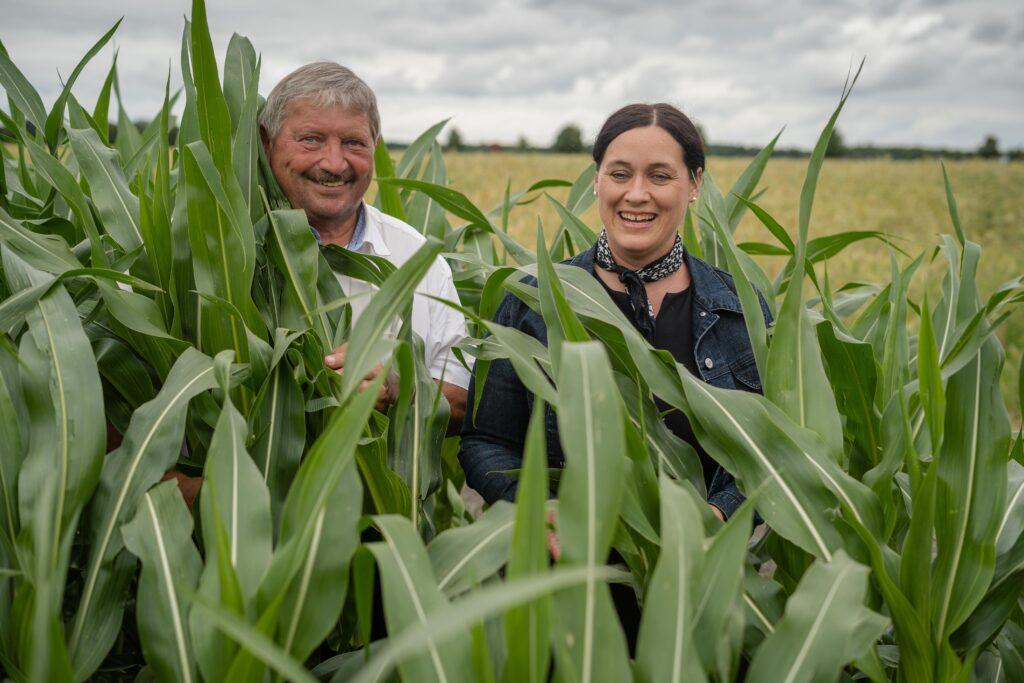 Georg Reitsberger der stellvertretende Landrat zeigt Birgit Obermaier ein Maisfeld